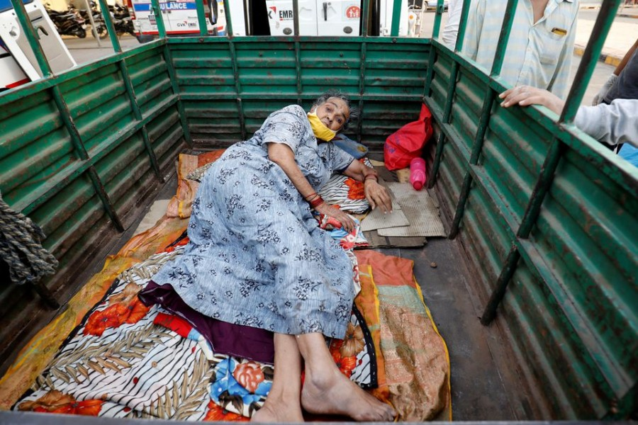 A woman lies in the back of a load carrier waiting to enter a COVID-19 hospital for treatment, amidst the spread of the coronavirus disease (COVID-19), in Ahmedabad, India, April 26, 2021. REUTERS/Amit Dave