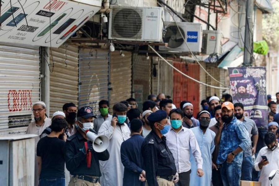 FILE PHOTO: A police officer uses megaphone to disperse shopkeepers, who gather to reopen their shops at a closed electronics market, as the lockdown continues during the efforts to stop the spread of the coronavirus disease (COVID-19), in Karachi, Pakistan April 27, 2020. REUTERS/Akhtar Soomro