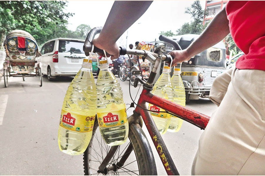 A man carries four bottles of soybean oil by his bicycle, as he makes his way home after buying the edible oil at a subsidised price from a sales point of TCB at Abdul Gani Road in the city on Tuesday — FE photo by Shafiqul Alam
