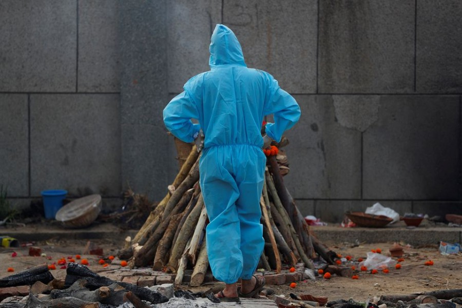 A man wearing personal protective equipment (PPE) stands next to a burning funeral pyre of a relative, who died from the coronavirus disease (Covid-19), before his cremation, at a crematorium in New Delhi, India on May 5, 2021 — Reuters photo