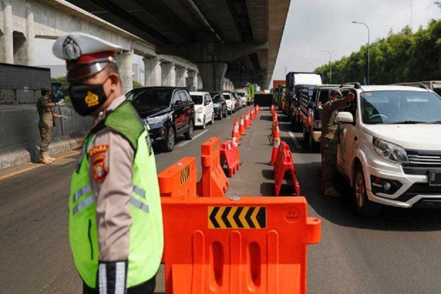 Police and municipality officers guard at a checkpoint on the first day of a national travel ban as Indonesia halts sea, land, air, and rail travel for the Eid-ul-Fitr celebrations in an effort to prevent a large-scale transmission of the coronavirus disease (COVID-19) pandemic, in Karawang, West Java province, May 6, 2021. REUTERS