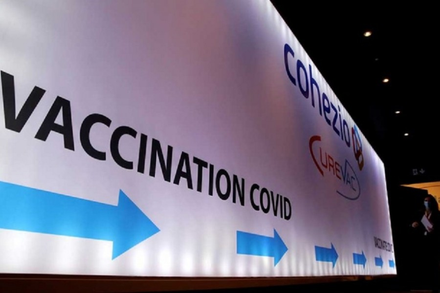 A woman walks past a board in a testing centre for the CureVac vaccine during a study by the German biotech firm CureVac as part of a testing for a new vaccine against the coronavirus disease (COVID-19), in Brussels, Belgium March 2, 2021. REUTERS