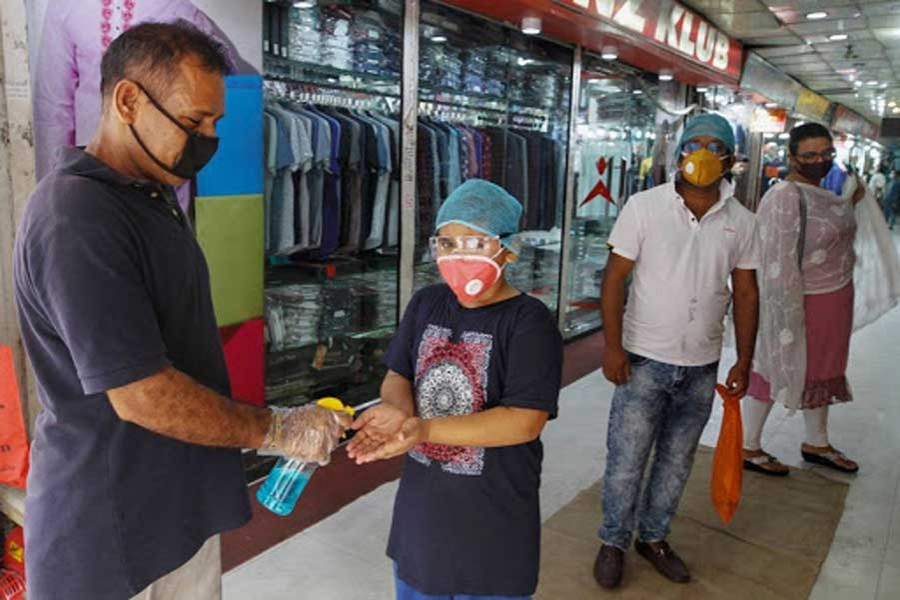 A staff gives a child hand sanitizer at a reopened market in Dhaka last year  —Xinhua photo