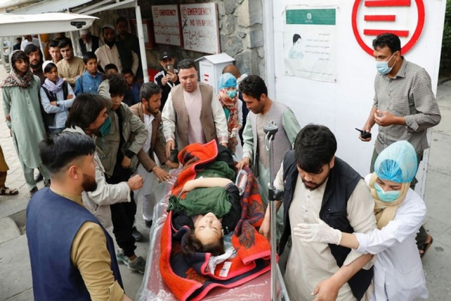 A woman being taken to a hospital following a bombing in Kabul on Saturday — Reuters