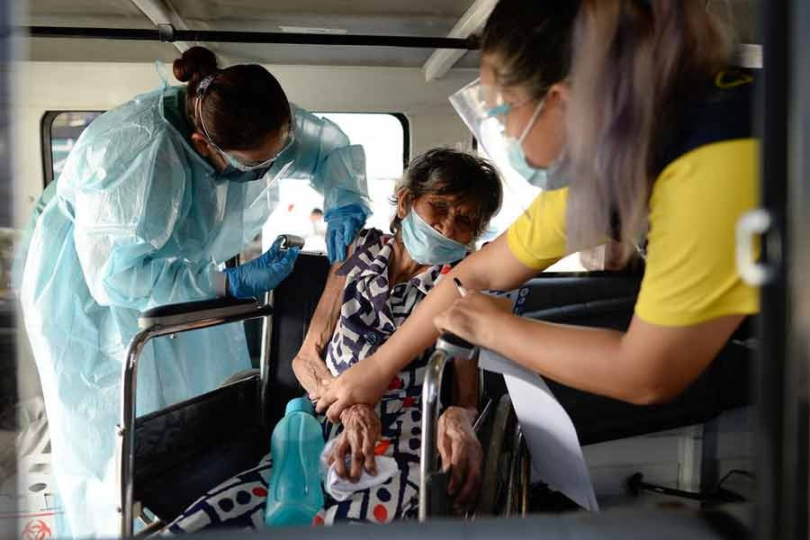 Felipa Tabladillo, 86, receiving a dose of China's Sinovac Biotech coronavirus disease (COVID-19) vaccine at a drive-thru vaccination site for bedridden and persons with disabilities in Metro Manila of Philippines on May 7 -Reuters file photo
