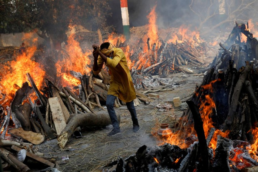 A man runs past the burning funeral pyres of those who died from the coronavirus disease (COVID-19), during a mass cremation, at a crematorium in New Delhi, India April 26, 2021. REUTERS/Adnan Abidi