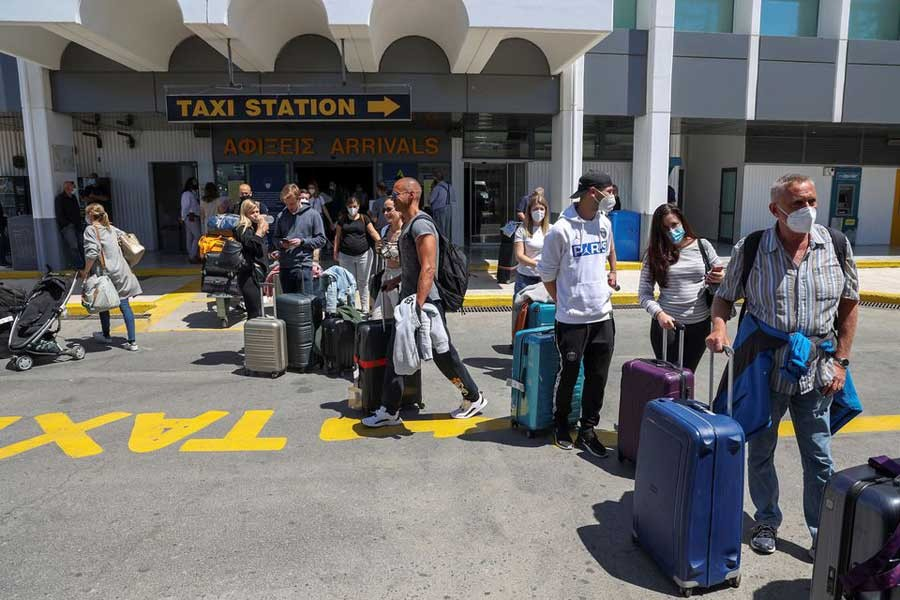 Passengers arriving from Germany and Switzerland standing with their luggage outside the terminal of the Heraklion airport, as the country's tourism season officially opens, on the island of Crete of Greece, on Saturday –Reuters photo