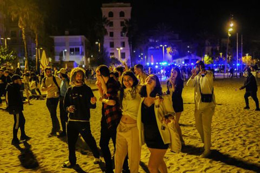 People gather in front of police officers patrolling Barceloneta beach, as the state of emergency decreed by the Spanish Government to prevent the spread of the coronavirus (COVID-19) was lifted a week ago in Barcelona, Spain, May 15, 2021. Picture taken May 15, 2021. REUTERS/Nacho Doce