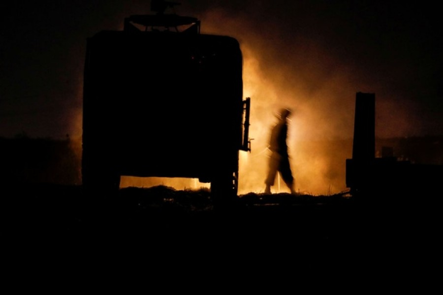 An Israeli soldier walks next to a military vehicle at a mobile artillery unit location on the Israeli side by the Israel border with Gaza May 16, 2021 - Reuters