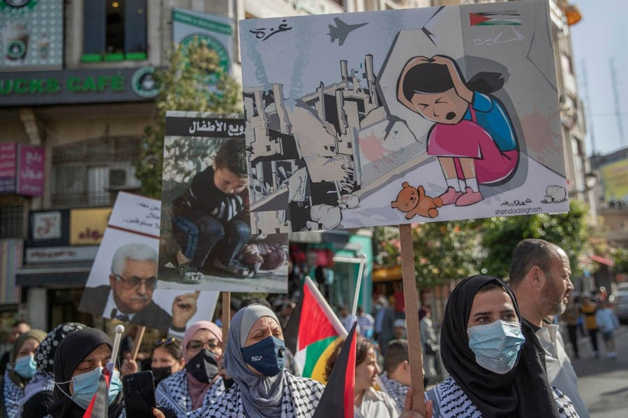 """Palestinian women carry posters that read """"no for terrorizing the children, Gaza, Palestine,"""" during a protest supporting the children in Gaza. —AP Photo"""