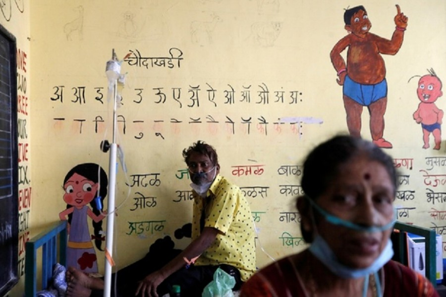 Patients suffering from coronavirus disease (COVID-19) receive oxygen support as they sit inside a classroom turned COVID-19 care facility on the outskirts of Mumbai, India, May 24, 2021. REUTERS