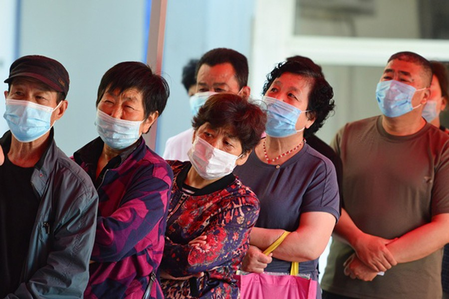 People wait in a line to get vaccinated with Sinopharm COVID-19 vaccine at the vaccination clinic of Gulou community health service center in Fuyang City. Reuters