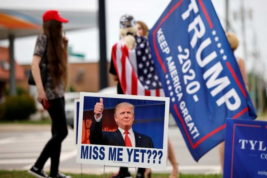 """Supporters of former US President Donald Trump gather on a street corner near a sign saying """"Miss Me Yet???"""" outside the North Carolina GOP convention before Trump was expected to speak at the gathering in Greenville, North Carolina, US June 5, 2021. REUTERS"""