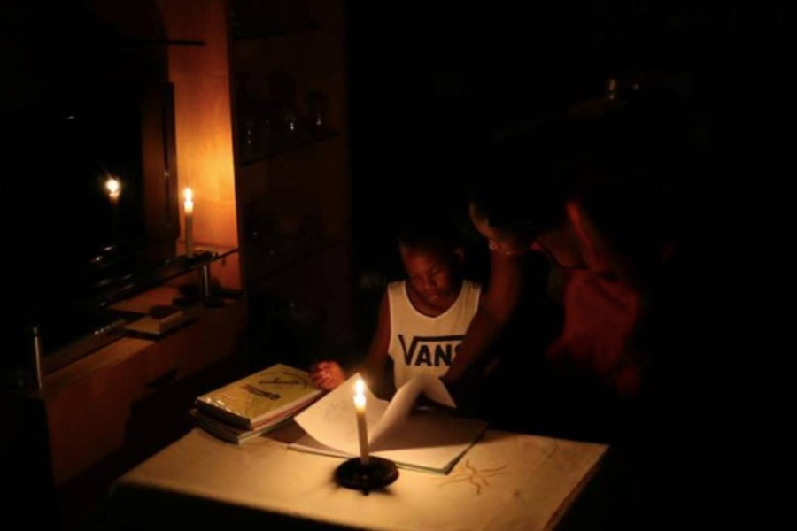 Nokuthula Thwala helps her nephew, Ayanda, with school work while using a candle during load shedding in Soweto, South Africa on February 2, 2020 — Reuters/Files