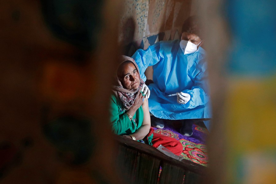 A shepherd woman is reflected as she receives a dose of COVISHIELD, a coronavirus disease (Covid-19) vaccine manufactured by Serum Institute of India, inside her hut during a vaccination drive at a forest area in south Kashmir's Pulwama district on June 7, 2021 — Reuters photo