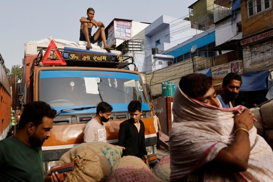 Workers load sacks of spices onto a truck at a wholesale market after authorities eased lockdown restrictions that were imposed to slow the spread of the coronavirus disease (COVID-19), in the old quarters of Delhi, India, June 8, 2021. Reuters