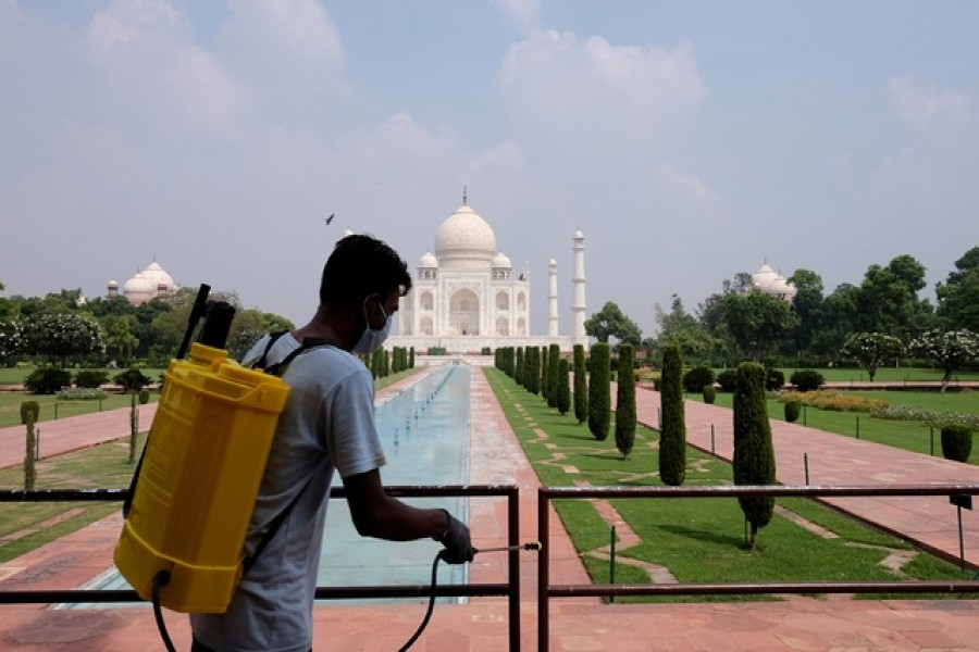A man sanitizes railings in the premises of Taj Mahal after authorities reopened the monument to visitors, amidst the coronavirus disease (COVID-19) outbreak, in Agra, India, Sept 21, 2020. REUTERS/FILE