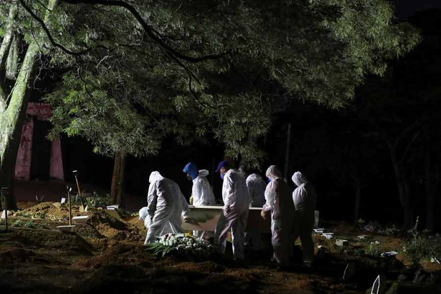 Gravediggers wearing protective suits carrying a coffin as spotlights illuminate the graves during a night burial at Vila Formosa cemetery, amid the coronavirus disease (COVID-19) pandemic, in Sao Paulo of Brazil on April 28 this year -Reuters file photo