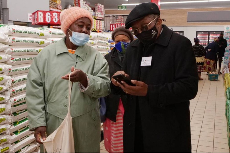 Bishop Malusi Mpumlwana, the general secretary of the South African Council of Churches, helps pensioner Phila Sheila Ngobeni register for a vaccine in Soweto, South Africa on June 3, 2021 — Thomson Reuters Foundation photo