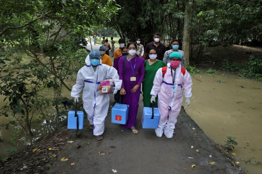 Healthcare workers carry COVISHIELD vaccine, a coronavirus disease (Covid-19) vaccine manufactured by Serum Institute of India, to inoculate villagers during a door-to-door vaccination and testing drive at Uttar Batora Island in Howrah district in West Bengal state, India on June 21, 2021 — Reuters photo