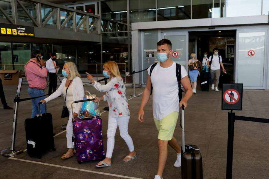 Tourists wearing protective face masks walk with their luggage as they arrive at Malaga-Costa del Sol Airport, in Malaga on Spain, June 7, 2021 — Reuters/Files