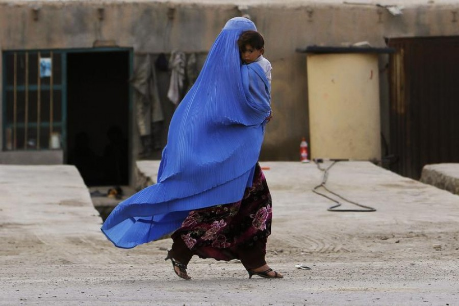 An Afghan woman wearing a burqa holds her child as she walks along a street on the outskirts of Kabul on May 13, 2013 — Reuters/Files