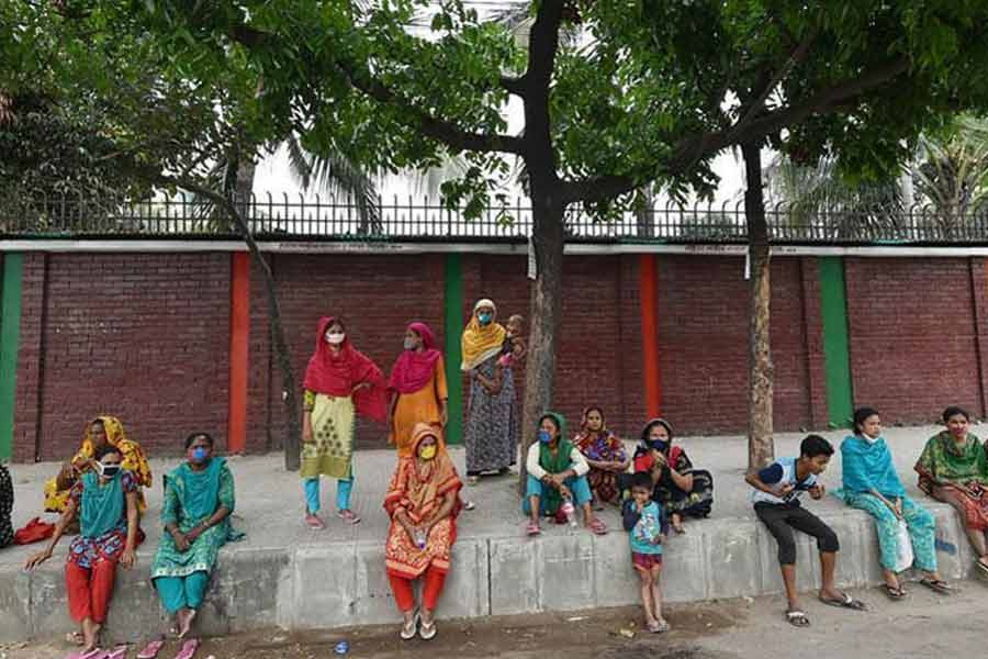 Low-income people hit hard by Covid-19 outbreak wait for collecting relief materials amid a shutdown in Dhaka.  —Xinhua Photo