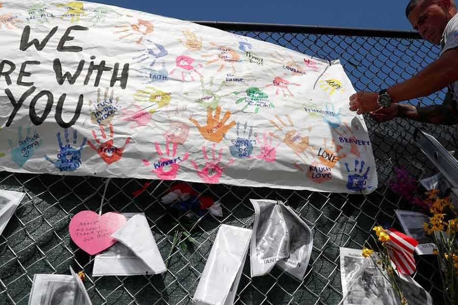 A member of the Miami-Dade Fire Rescue unit placing a sign on a makeshift memorial for the victims of the Surfside's Champlain Towers South condominium collapse in Miami of US on July 8 -Reuters file photo