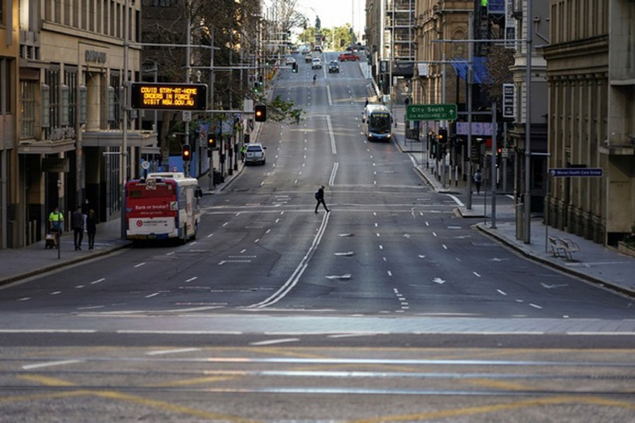 A pedestrian crosses an unusually quiet street in the city centre during a lockdown to curb the spread of the coronavirus disease (COVID-19) in Sydney, Australia, July 5, 2021. REUTERS