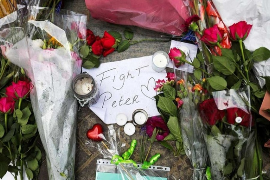 Flowers and a note rest on the place where Dutch celebrity crime reporter Peter R de Vries has been shot and reported seriously injured in Amsterdam, Netherlands, July 7, 2021. REUTERS/Eva Plevier