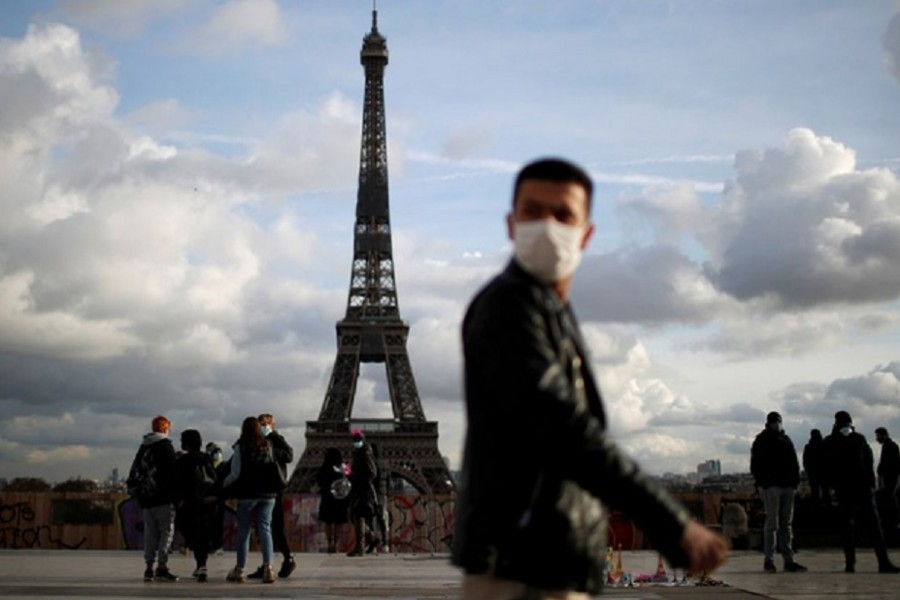 A man, wearing protective face mask, walks at Trocadero square near the Eiffel Tower in Paris amid the coronavirus disease (COVID-19) outbreak in France, Jan 22, 2021. REUTERS