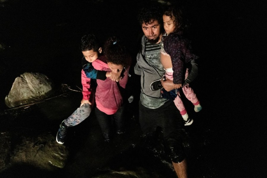 Asylum-seeking migrants' families from Ecuador walk in the water as they arrive to the bank of the Rio Grande river after crossing into the United States from Mexico in Roma, Texas, US, July 7, 2021 — Reuters