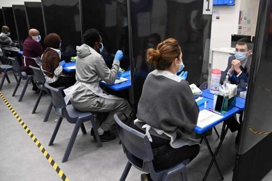 Health workers and volunteers assist as students take coronavirus disease (Covid-19) tests at Harris Academy Beckenham, ahead of full school reopening in England as part of lockdown restrictions being eased, in Beckenham, south east London, Britain, March 5, 2021 — Reuters