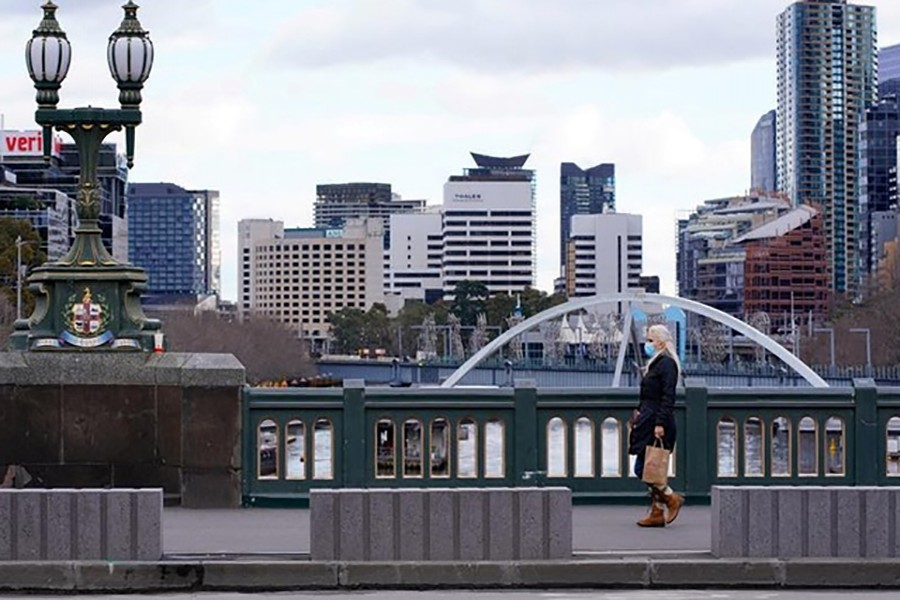 A lone woman, wearing a protective face mask, walks across an unusually quiet city centre bridge on the first day of a lockdown as the state of Victoria looks to curb the spread of a COVID-19 outbreak in Melbourne, Australia, July 16, 2021. REUTERS