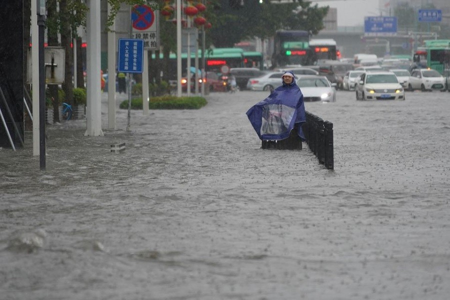 A resident wearing a rain cover stands on a flooded road in Zhengzhou, Henan province, China July 20, 2021 — cnsphoto via Reuters
