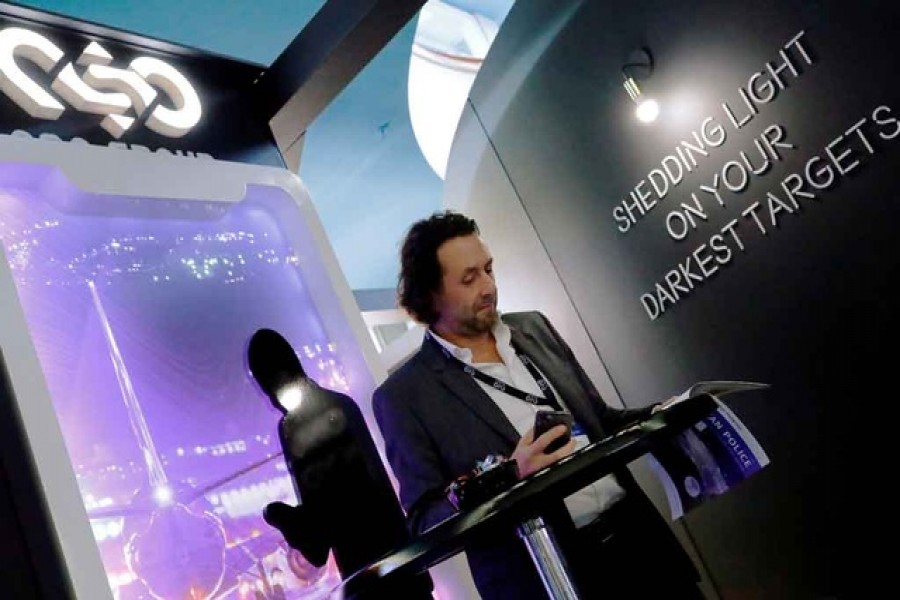 A man reads at a stand of the NSO Group Technologies, an Israeli technology firm known for its Pegasus spyware enabling the remote surveillance of smartphones, at the annual European Police Congress in Berlin, Germany, February 4, 2020. Reuters