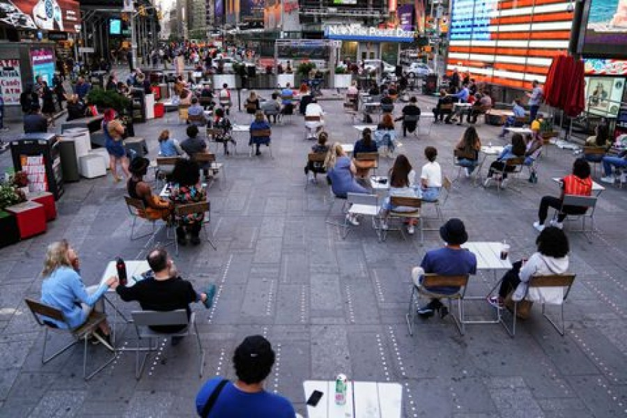 People sit physically distanced while watching a concert in Times Square in the Manhattan borough of New York City, New York, U.S., June 1, 2021. REUTERS/Carlo Allegri/File Photo