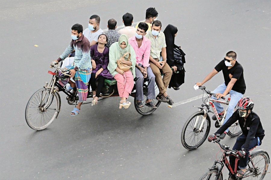 A group of people are travelling on a rickshaw van while two others are riding bicycles to their destinations. People who have to come out due to emergency rely on these modes of transport during the ongoing lockdown. The photo was taken in the Rayerbagh area on the Dhaka-Chattogram highway on Thursday — FE photo by Shafiqul Alam