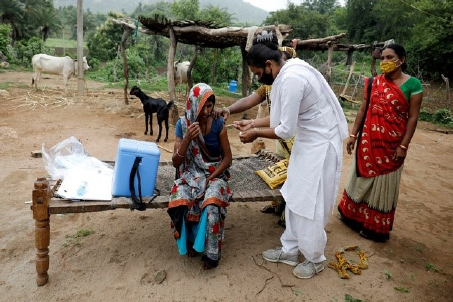 Healthcare worker Jankhana Prajapati gives a dose of the domestically manufactured COVISHIELD vaccine to villager Amiyaben Dabhi during a door-to-door vaccination drive in Banaskantha district in the western state of Gujarat, India, July 23, 2021 — Reuters/Files