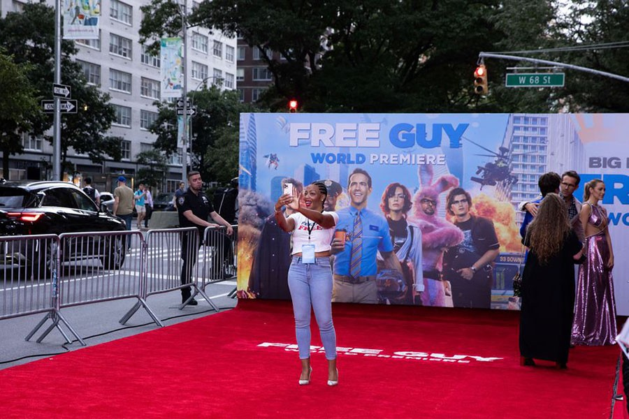 A guest takes a selfie on the red carpet at the premiere for the film 'Free Guy' in New York City, New York, U.S., August 3, 2021. Reuters