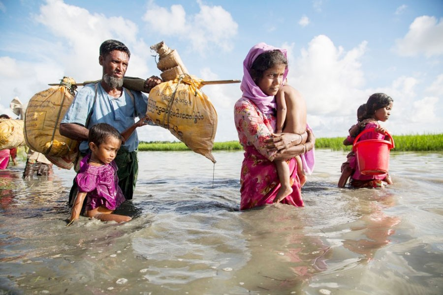 A Rohingya family wades through water crossing the border from Myanmar into Bangladesh. —UNHCR Photo