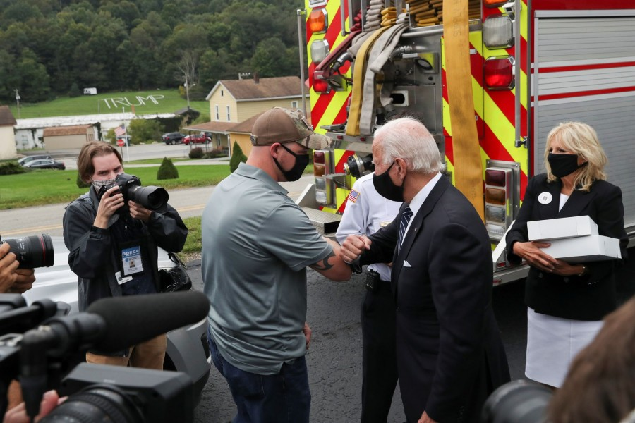 Democratic US presidential nominee and former Vice President Joe Biden elbow bumps a firefighter as he and his wife Jill deliver donuts and beer to firefighters at Shanksville fire station number 627 after visiting the nearby Flight 93 National Memorial to those killed when hijacked Flight 93 crashed into an open field on September 11, 2001, in Shanksville, Pennsylvania, September 11, 2020. REUTERS/Leah Millis