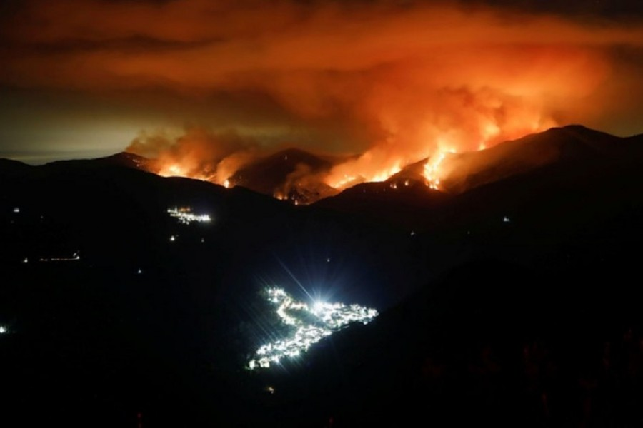 A wildfire is seen at night on Sierra Bermeja Mountain, near the towns of Genalguacil (L) and Benarraba (bottom), southern Spain, September 10, 2021. Picture taken with a long exposure. REUTERS/Jon Nazca
