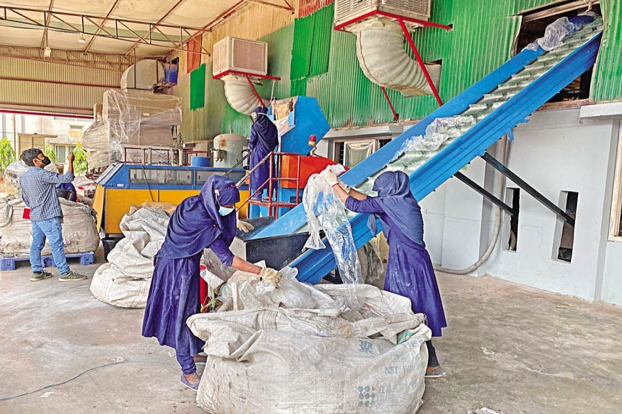 Workers putting used plastics on a conveyor belt for crushing at the recycling plant of Pran-RFL Group in Habiganj — FE Photo