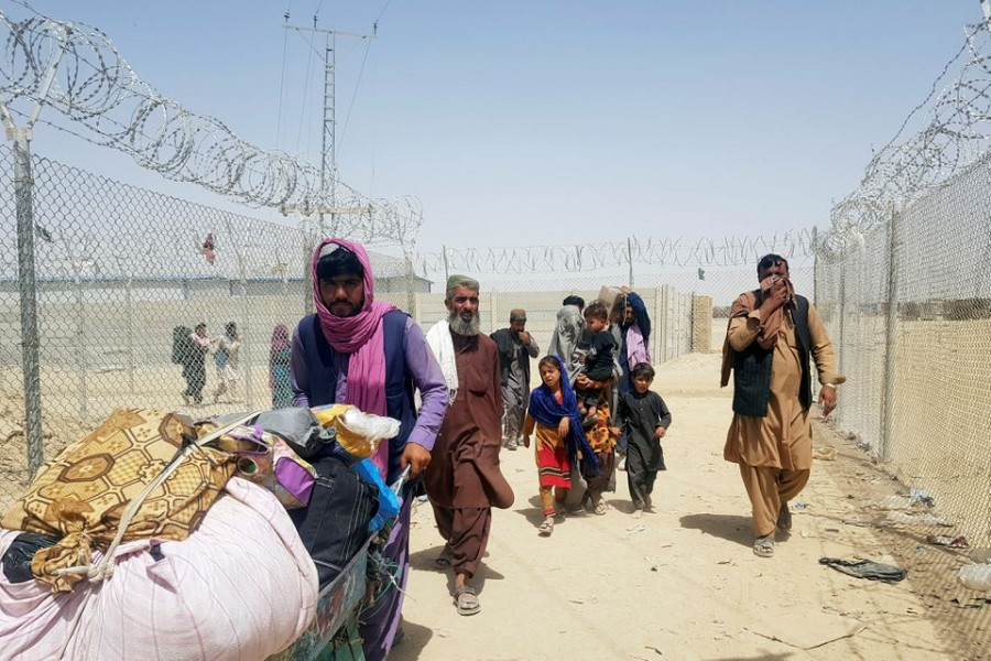 A family from Afghanistan walk next to fence to cross into Pakistan at the Friendship Gate crossing point, in the Pakistan-Afghanistan border town of Chaman, Pakistan on September 6, 2021 — Reuters/Files