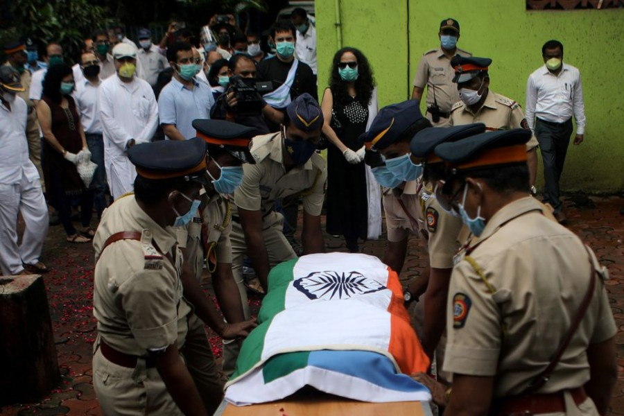 Police personnel carry the coffin of deceased Air India pilot Deepak Sathe as family members look on during his funeral in Mumbai, India on August 11, 2020 — Reuters/Files