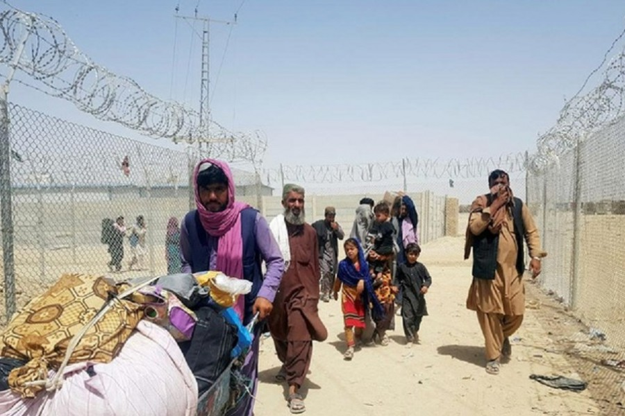 A family from Afghanistan walk next to fence to cross into Pakistan at the Friendship Gate crossing point, in the Pakistan-Afghanistan border town of Chaman, Pakistan September 6, 2021. REUTERS/Abdul Khaliq Achakzai