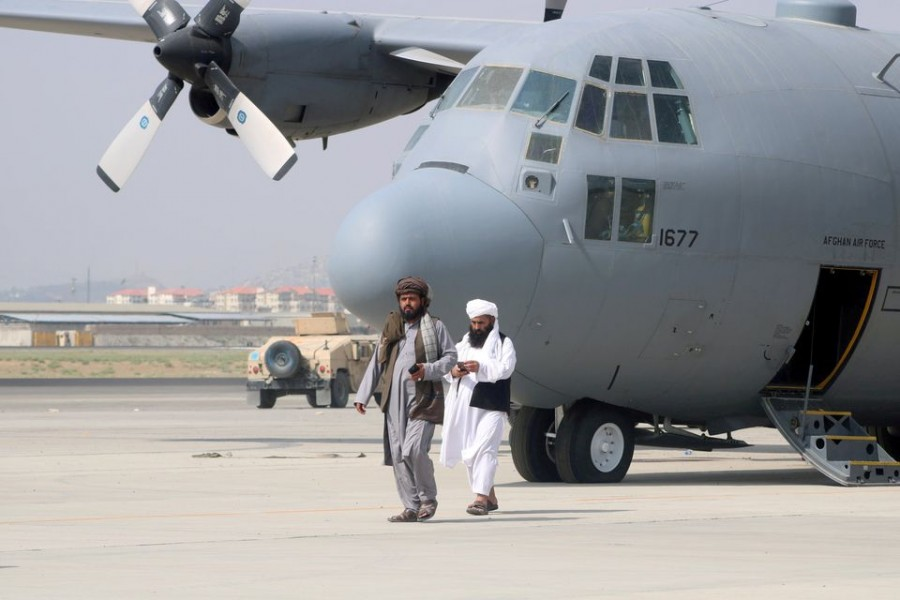 Taliban walk in front of a military airplane a day after the US troops withdrawal from Hamid Karzai International Airport in Kabul, Afghanistan August 31, 2021. REUTERS/Stringer