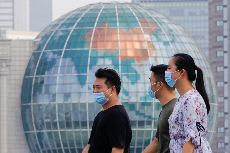 People wearing protective face masks walk along The Bund in front of the Lujiazui financial district of Pudong, following new cases of the coronavirus disease (COVID-19), in Shanghai, China August 25, 2021. REUTERS/Aly Song