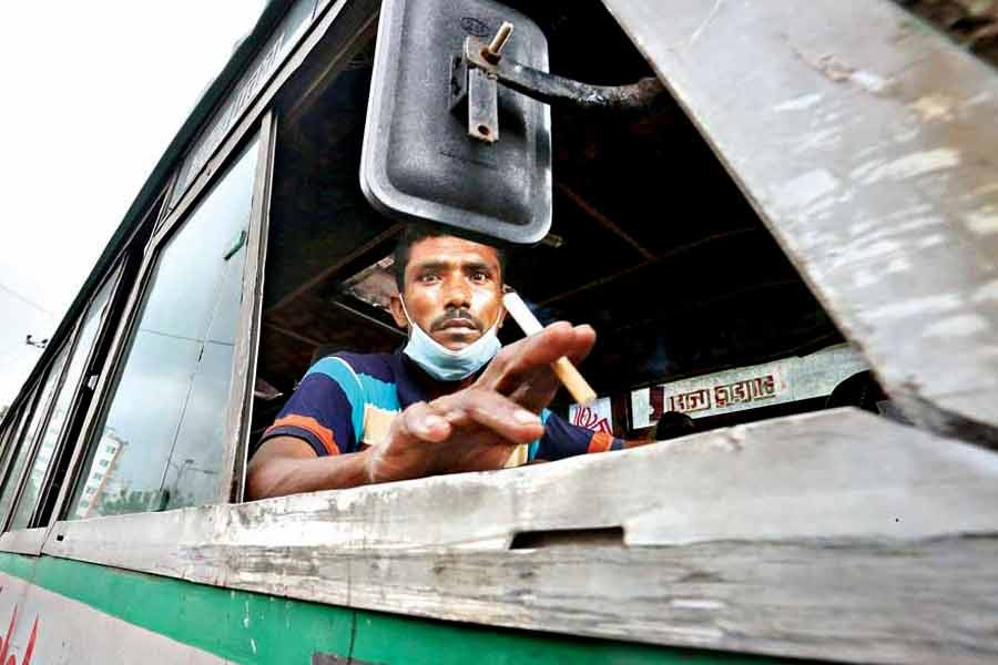 With his mask hanging under his chin, a bus driver smoking while driving, which poses health risks to the passengers. The photo of the driver flouting the health safety rules was taken in Khilgaon area of the city amid COVID-19 pandemic last year —FE file photo